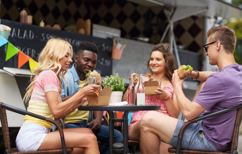 Amis heureux avec des boissons mangeant au camion de nourriture photos libres de droits