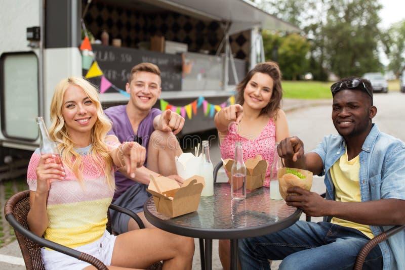 Amis heureux avec des boissons mangeant au camion de nourriture images libres de droits