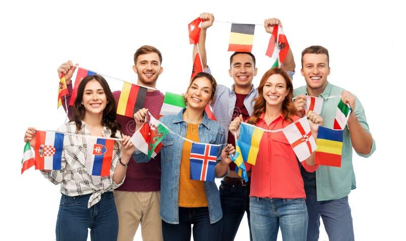 Amis heureux avec des drapeaux de différents pays images stock