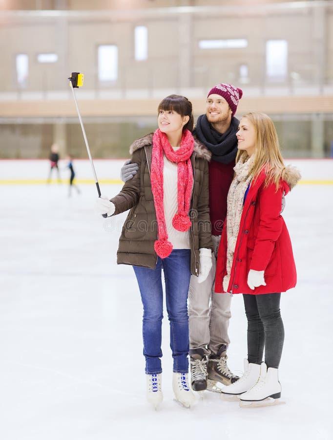 Amis heureux avec le smartphone sur la piste de patinage photo libre de droits