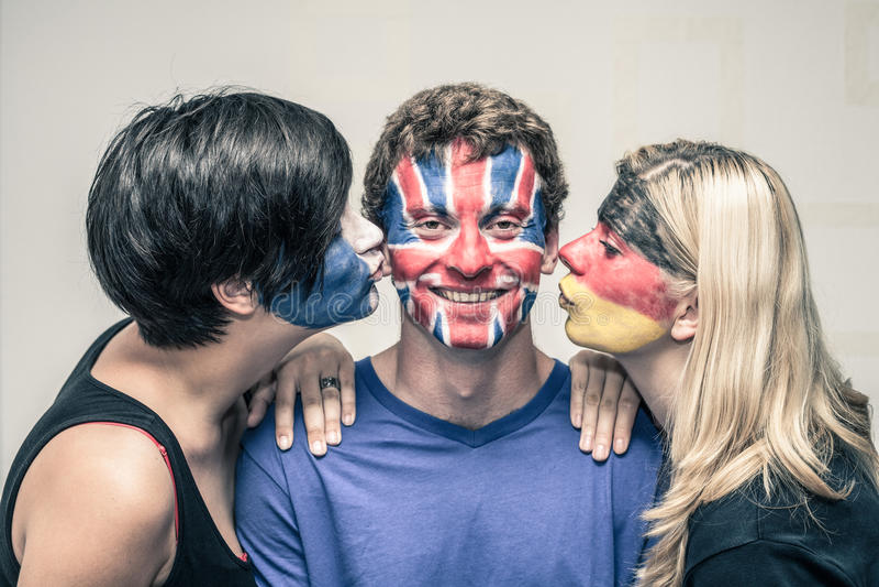Amis heureux avec les drapeaux peints sur des baisers de visages photos libres de droits