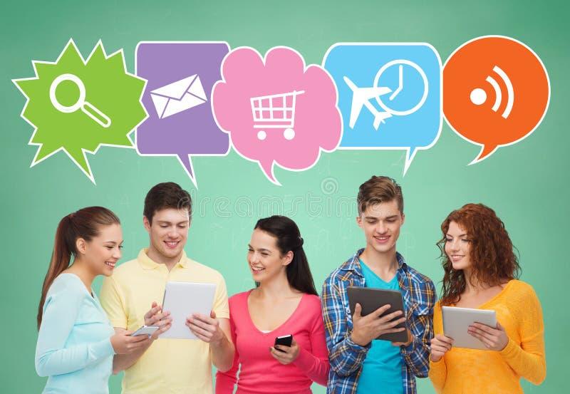 Amis heureux avec les smartphones et le PC de comprimé photos libres de droits