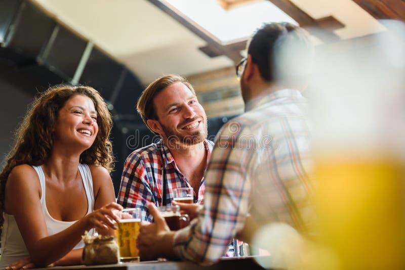 Amis heureux ayant l'amusement à la barre - bière potable de jeunes à la mode et riant ensemble images libres de droits