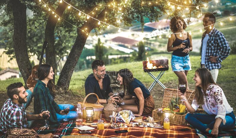 Amis heureux ayant l'amusement au vignoble après coucher du soleil - camping millénaire des jeunes au pique-nique d'air ouvert so photo libre de droits