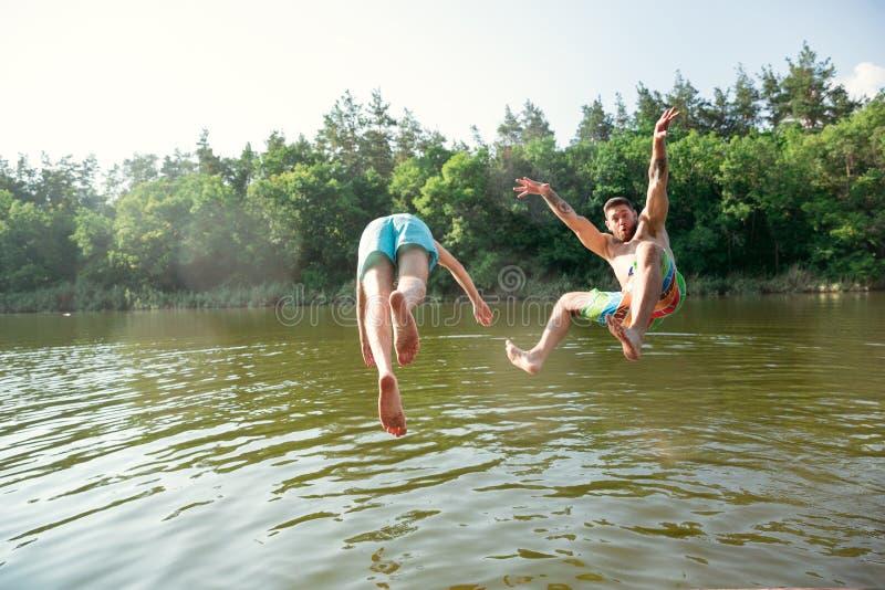 Amis heureux ayant l'amusement, prêt à sauter et nager en rivière image stock