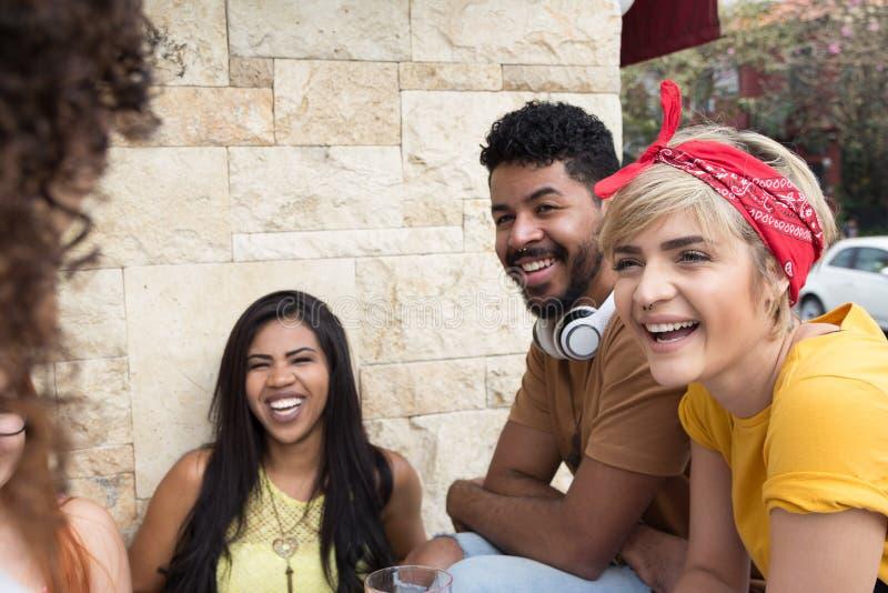 Amis heureux ayant une vie sociale en partie au restaurant dehors Résumé images libres de droits