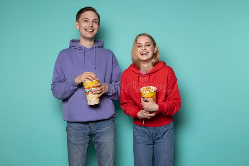 Amis heureux, belle fille blonde et type dans le hoodie pourpre observant un film de comédie avec le maïs éclaté dans des mains photo stock