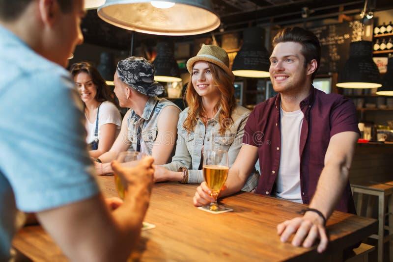 Amis heureux buvant de la bière et parlant à la barre photos stock