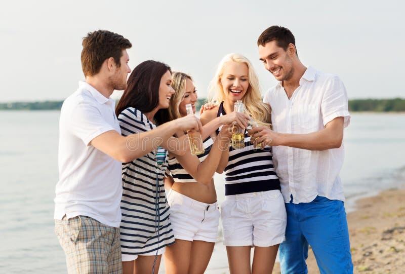 Amis heureux buvant de la bière non alcoolique sur la plage photographie stock libre de droits