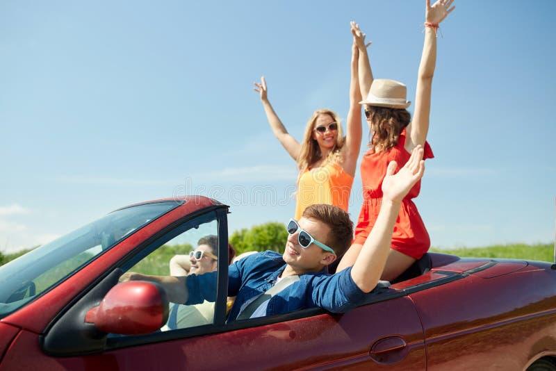 Amis heureux conduisant dans la voiture de cabriolet au pays photos stock