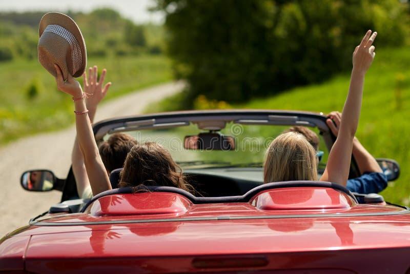 Amis heureux conduisant dans la voiture de cabriolet au pays photo libre de droits