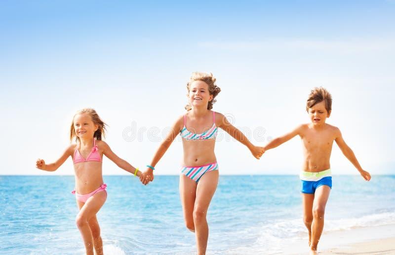 Amis heureux courant ensemble le long de la plage sablonneuse photographie stock libre de droits