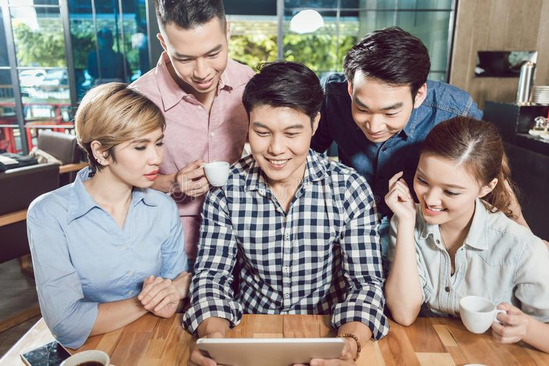 Amis heureux dans le café regardant le comprimé numérique photographie stock