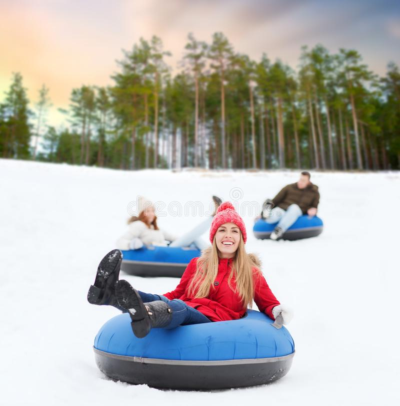 Amis heureux glissant en bas de la colline sur des tubes de neige image stock
