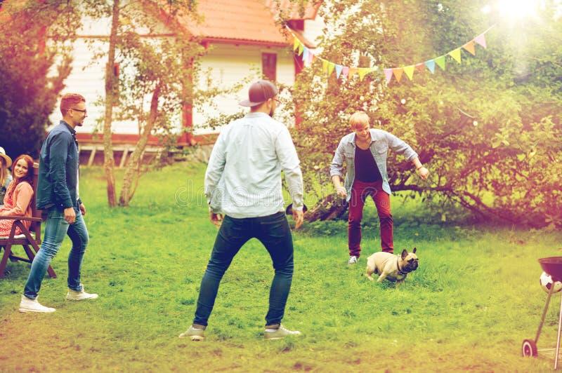 Amis heureux jouant avec le chien au jardin d'été photo stock