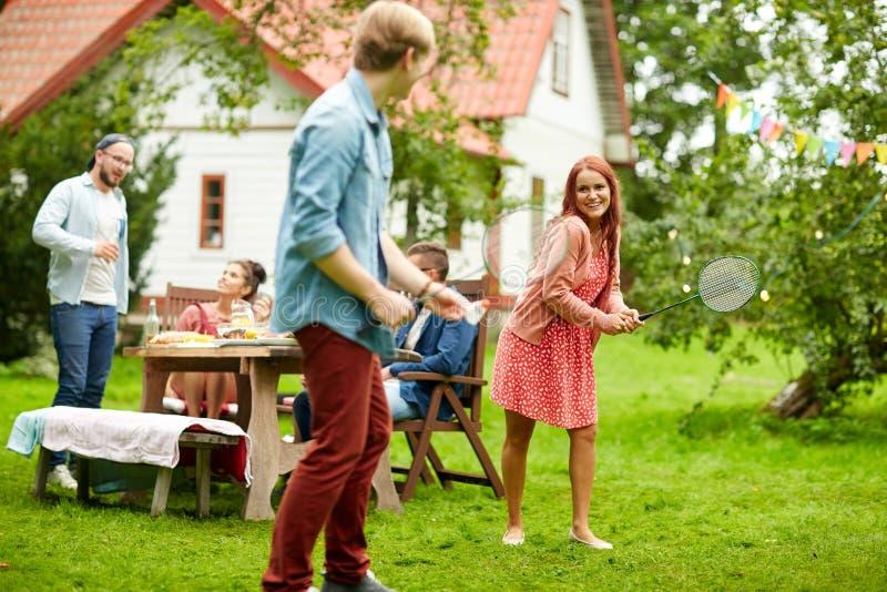 Amis heureux jouant le badminton au jardin d'été photo stock