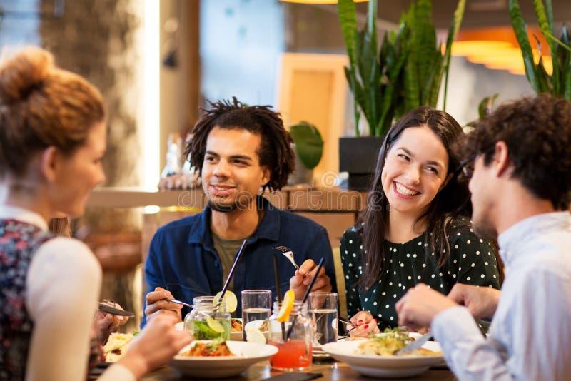 Amis heureux mangeant au restaurant images libres de droits