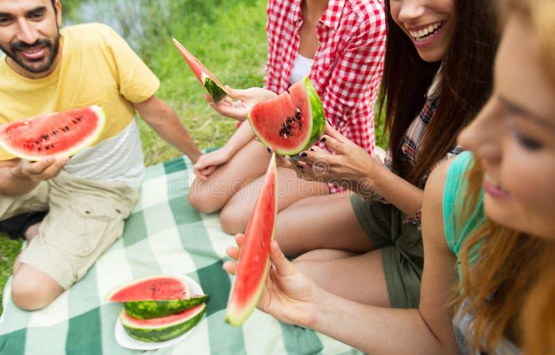 Amis heureux mangeant la pastèque au camping image libre de droits