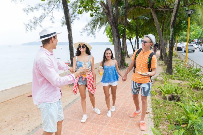 Amis heureux marchant ensemble en parc près du jeune groupe de personnes de mer sur des vacances et la communication de touristes photographie stock libre de droits