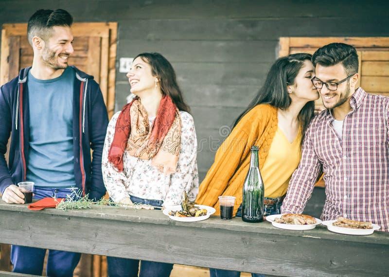 Amis heureux prenant le déjeuner à l'arrière-cour mangeant de la viande grillée et buvant du vin rouge - deux couples des amants  photos stock