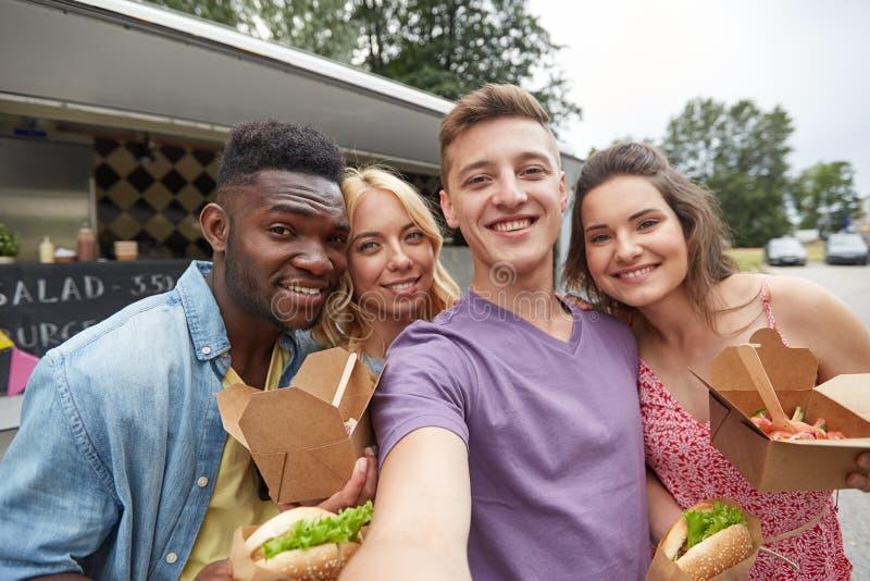Amis heureux prenant le selfie au camion de nourriture image libre de droits