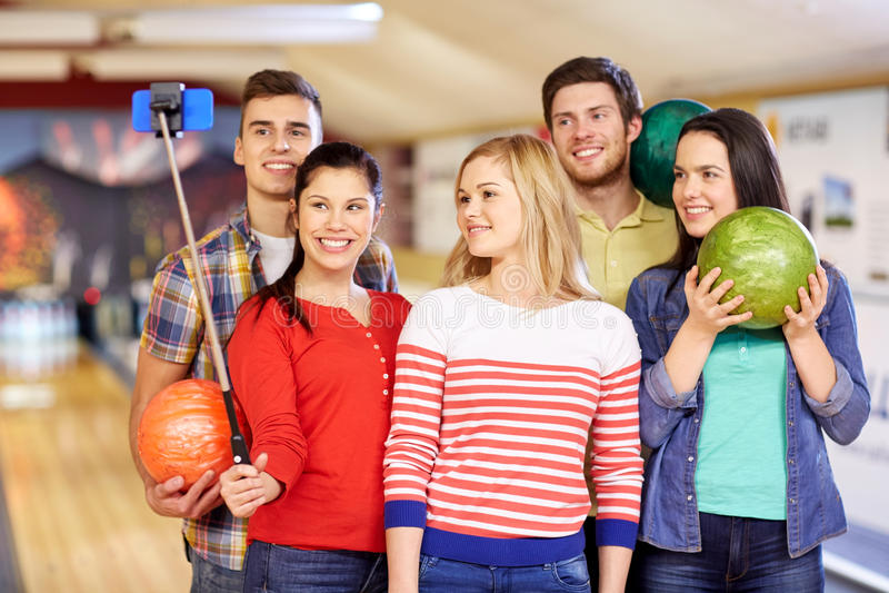 Amis heureux prenant le selfie dans le club de bowling photo libre de droits