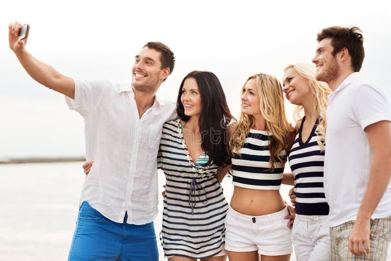 Amis heureux prenant le selfie sur la plage d'été photos stock