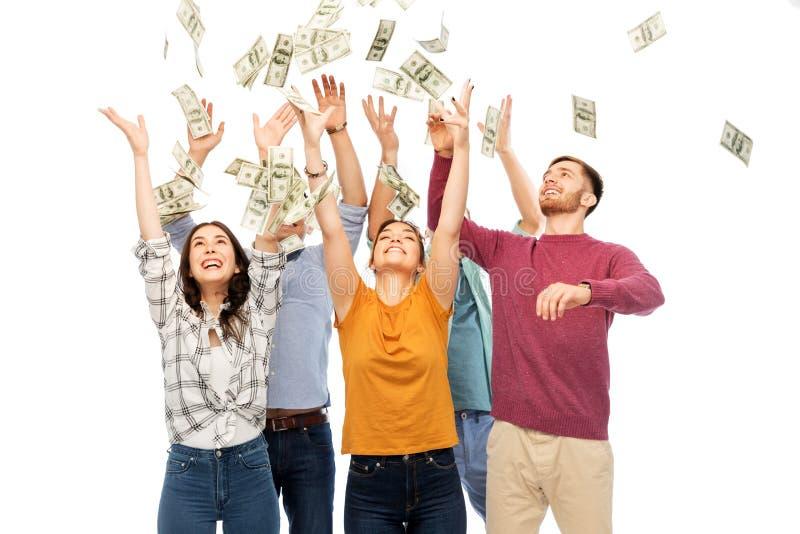 Amis heureux s?lectionnant l'argent tombant de en haut photographie stock