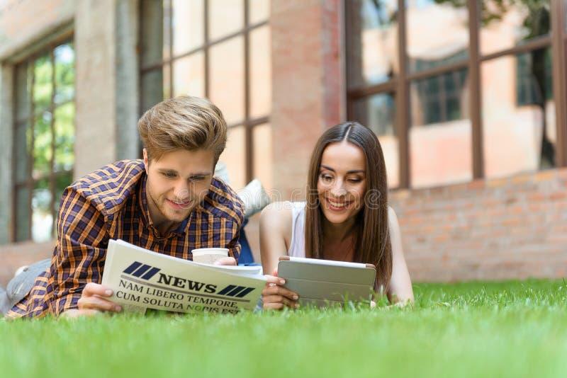 Amis heureux se reposant sur la pelouse image libre de droits
