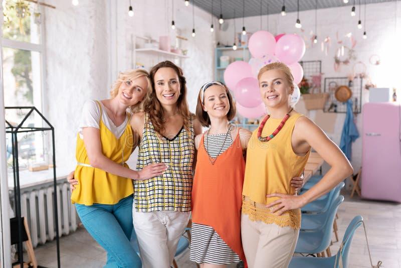 Amis heureux se tenant près de leur ami enceinte dans la boulangerie images libres de droits
