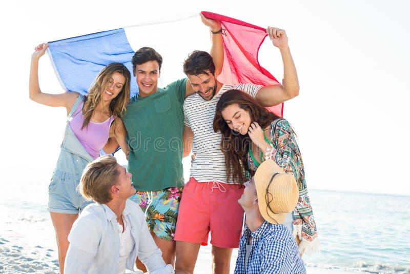 Amis heureux tenant le drapeau français sur le rivage image stock