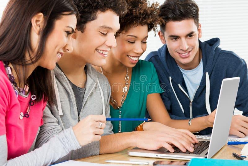 Amis heureux travaillant sur l'ordinateur portable photo stock