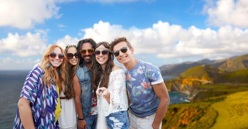Amis hippies prenant la photo par le bâton de selfie photos stock