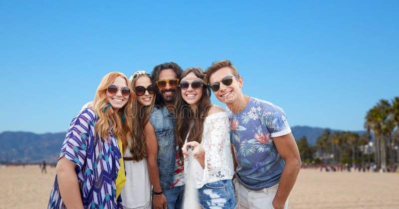 Amis hippies prenant la photo par le bâton de selfie image stock