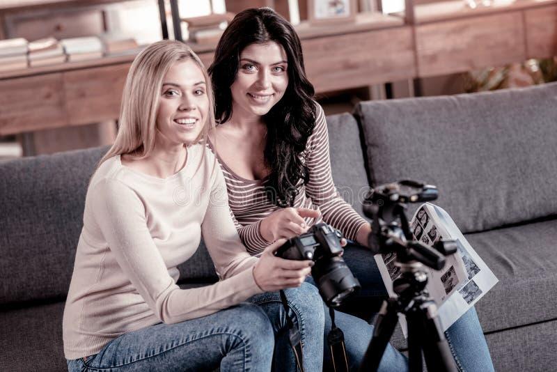 Amis inspirés s'asseyant sur le divan photographie stock