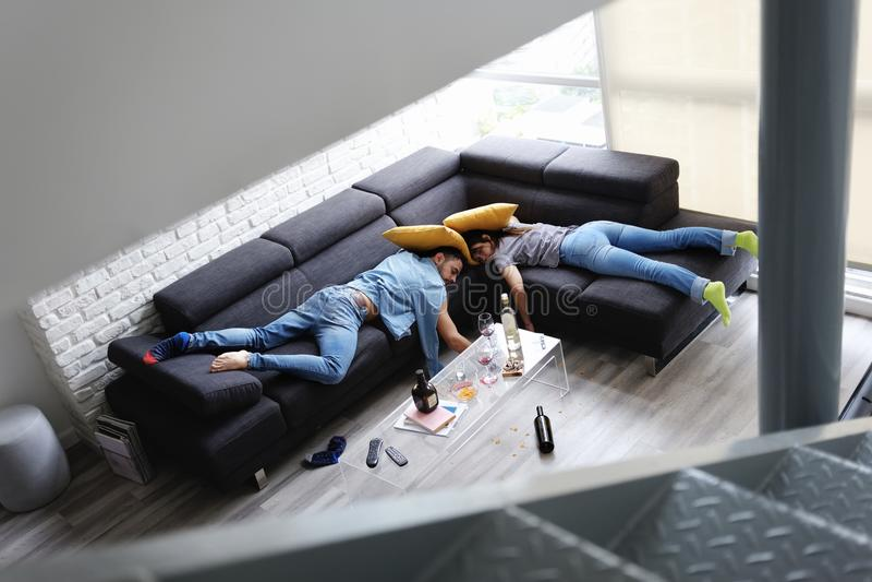 Amis ivres dormant sur la partie de Sofa In Messy Room After images libres de droits