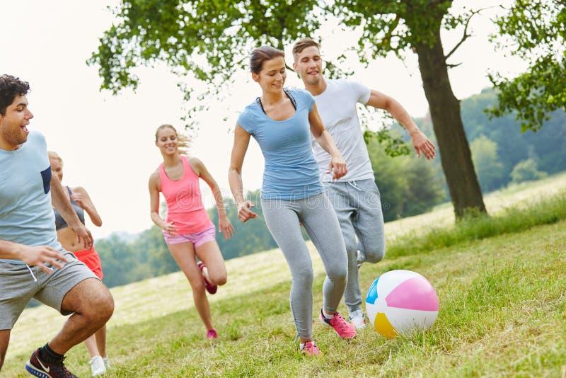 Amis jouant avec la boule dans le mouvement photos stock