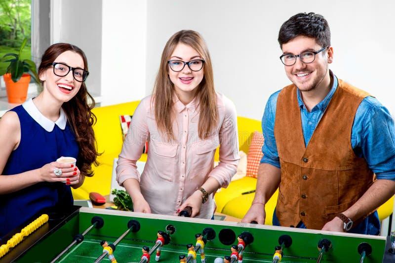 Amis jouant le football de table image stock