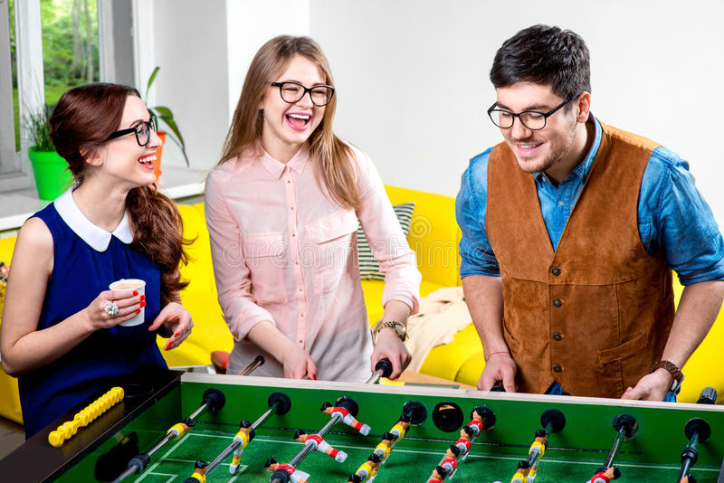 Amis jouant le football de table images stock