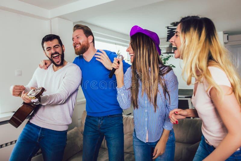 Amis jouant le karaoke ? la maison Concept au sujet de l'amiti?, du Home Entertainment et des personnes image libre de droits