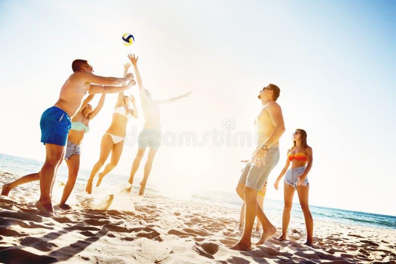 Amis jouant le temps de coucher du soleil de voleyball de plage image stock