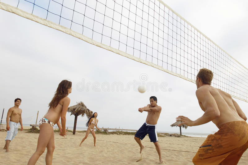 Amis jouant le volleyball sur la plage image stock