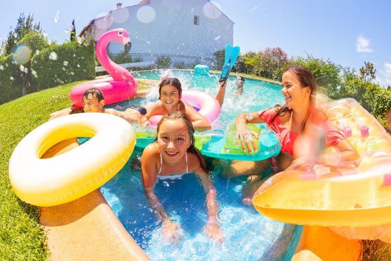 Amis joyeux jouant dans la piscine extérieure images libres de droits