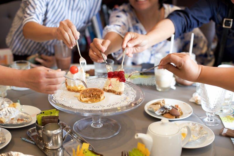 Amis mûrs ayant le gâteau et la boisson sur l'anniversaire photo libre de droits