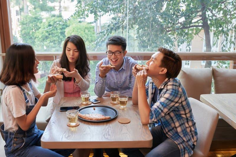 Amis mangeant de la pizza en café images libres de droits