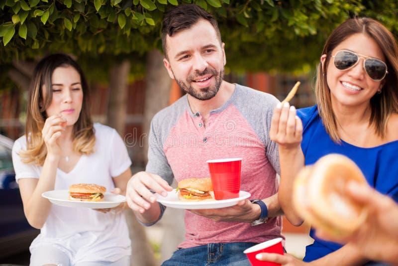 Amis mangeant des hamburgers et ayant l'amusement images libres de droits