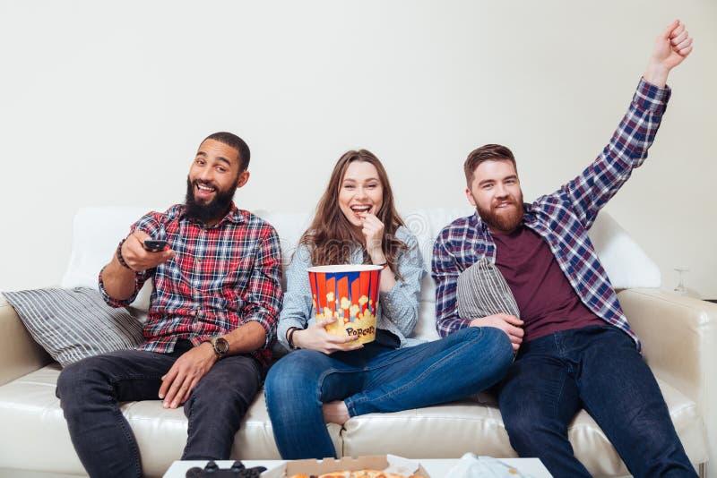 Amis mangeant du maïs éclaté et regardant la TV ensemble photo stock