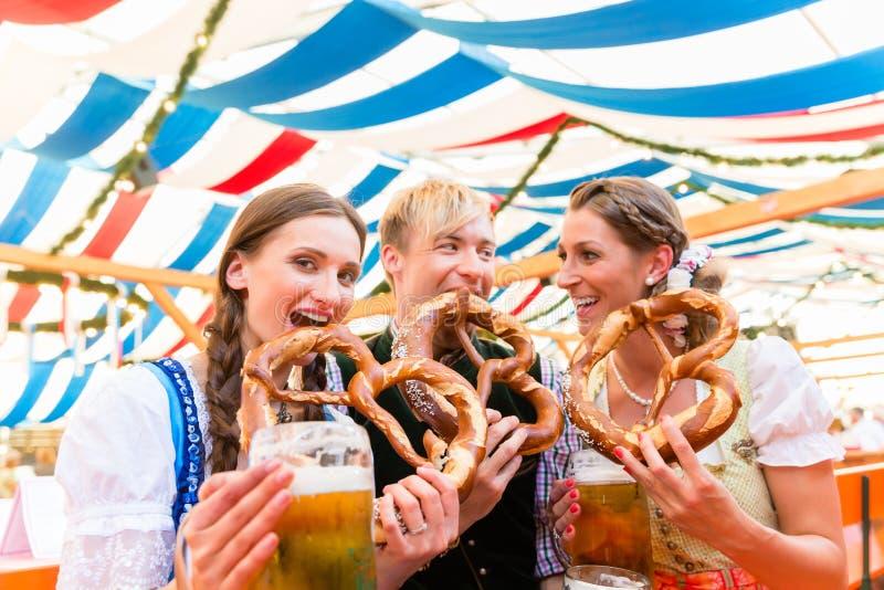 Amis mangeant les bretzels géants et buvant dans la tente de bière image libre de droits