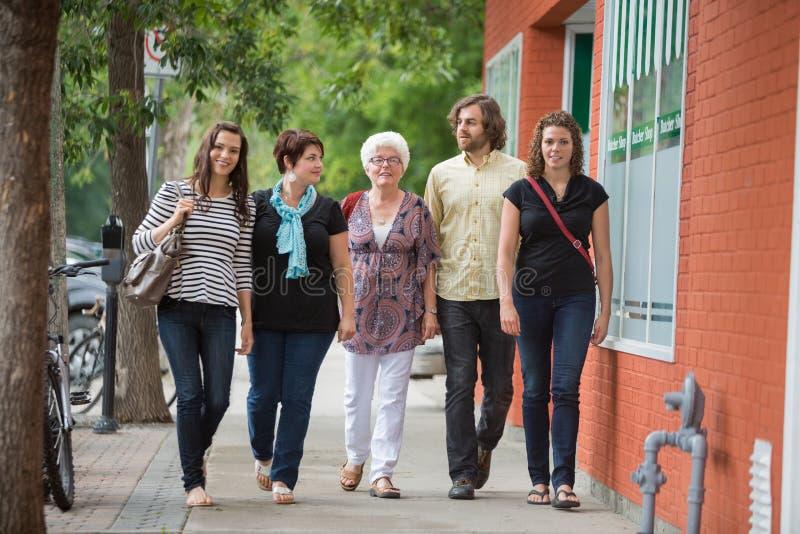 Amis marchant ensemble sur le trottoir image stock