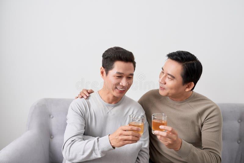 Amis masculins asiatiques et se reposer sur le sofa et le whiskey potable photo libre de droits